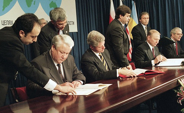 Russian President Boris Yeltsin, left, American President Bill Clinton, Ukrainian President Leonid Kuchma, and British Prime Minister John Major, extreme right, sign the Nuclear N